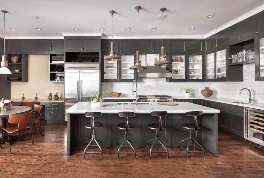 Contemporary kitchen with dark gray cabinets, white quartz countertops, pendant lights and wood flooring