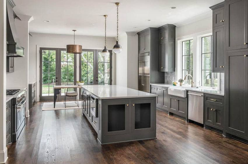Contemporary kitchen with dark gray island and cabinets with white quartz counters pendant lights