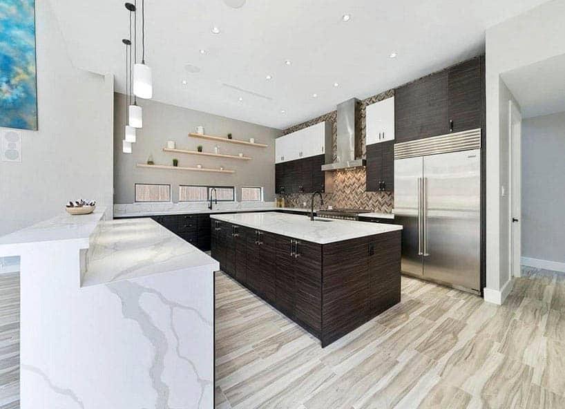 Contemporary kitchen with island and peninsula quartz countertops dark veneer cabinets