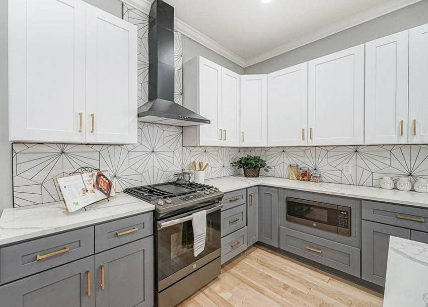 Contemporary kitchen with white and dark gray cabinets with gold hardware pattern tile backsplash