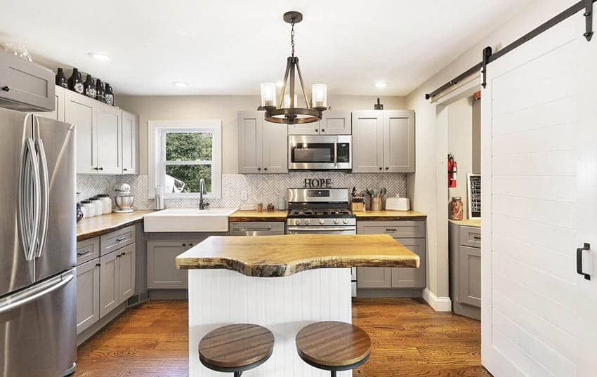 Famrhouse kitchen with small beadboard island and live edge wood countertop