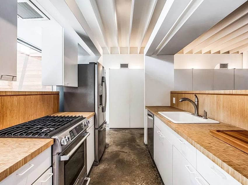 Galley kitchen with bamboo countertops white cabinets concrete flooring