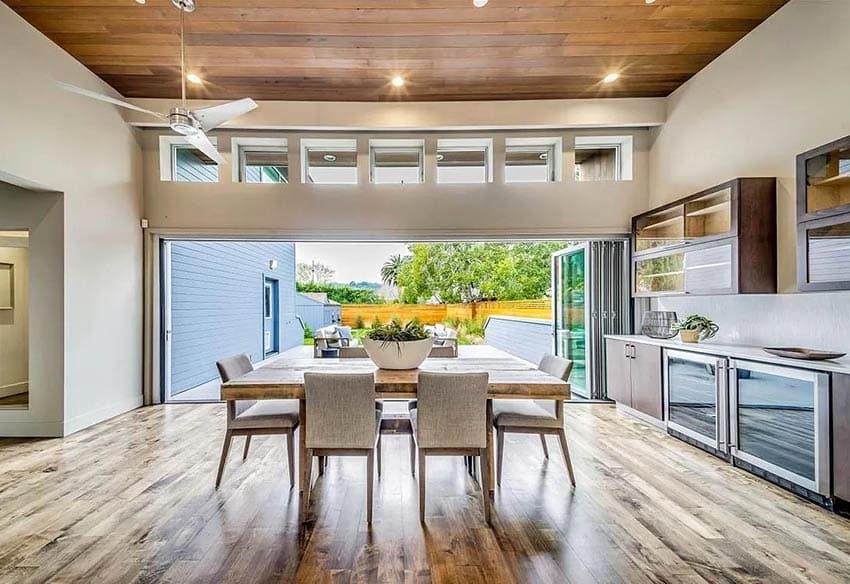 Indoor outdoor living room with clerestory windows wood plank ceiling