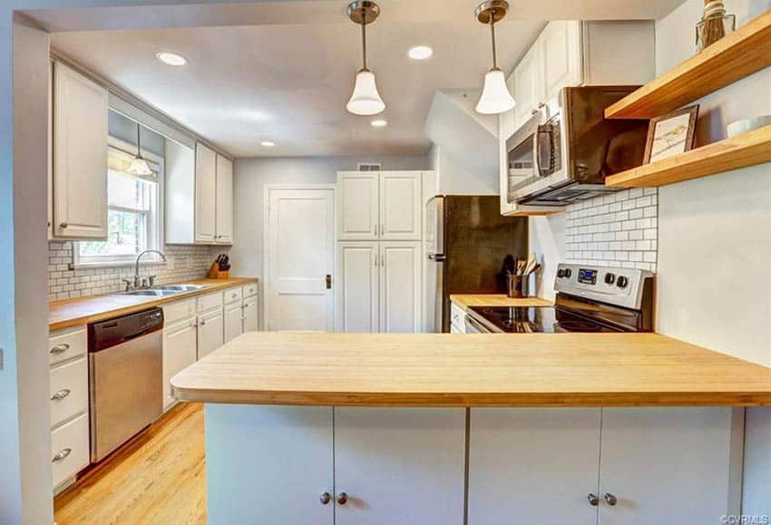 Kitchen with bamboo countertops peninsula white cabinets subway tile