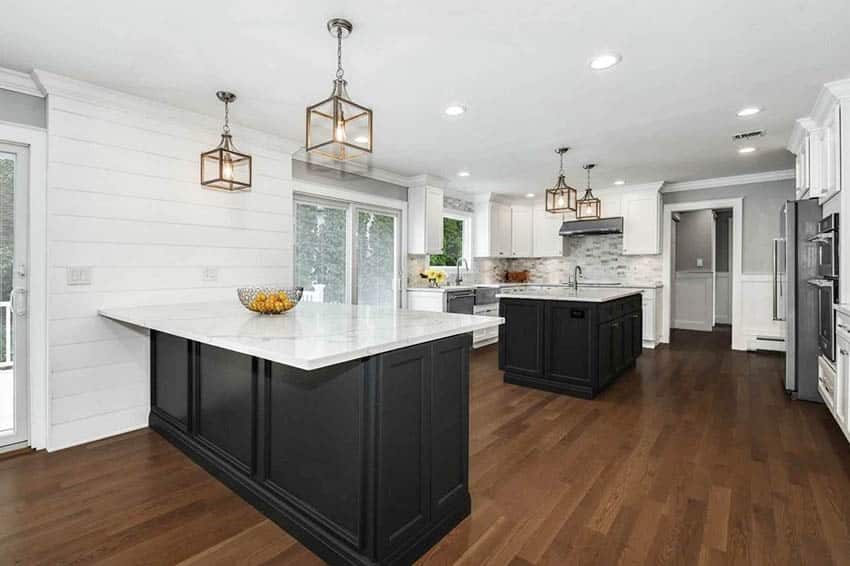 Kitchen with black island and peninsula white cabinets quartz countertops shiplap walls