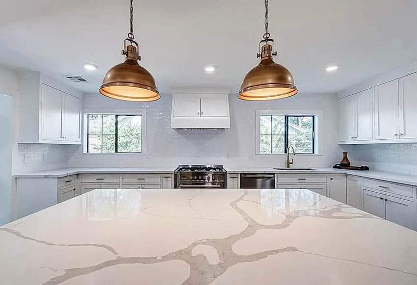 Kitchen with calacatta countertops, island, white cabinets and gold pendant lights