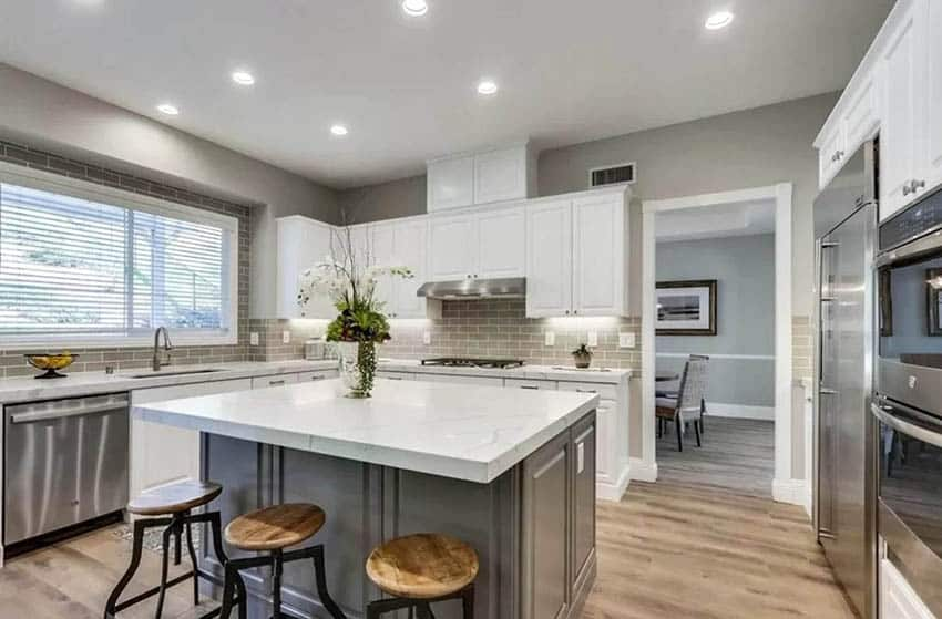 Kitchen with dark gray cabinet island and white cabinets
