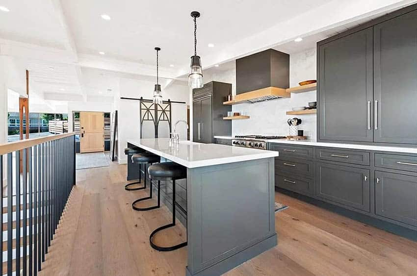 Kitchen with dark gray painted cabinets white quartz countertops wood flooring