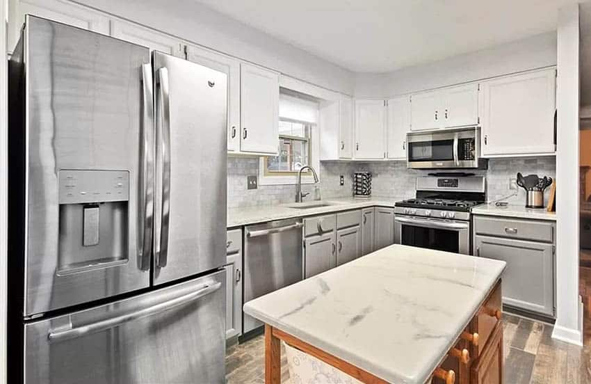 Kitchen with epoxy countertops, white cabinets, stainless steel appliances and wood flooring