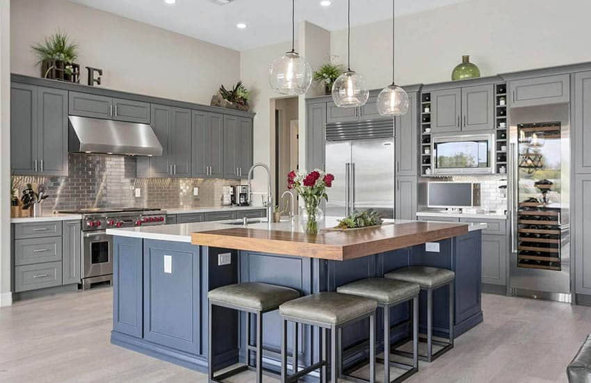 Kitchen with gray cabinets and blue gray island with white quartz and butcher block counters