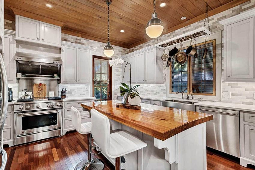 Kitchen with heart of pine reclaimed wood island, white cabinets and Brazilian mahogany flooring