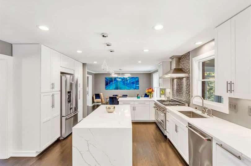 Kitchen with quartz waterfall island and small peninsula white cabinets