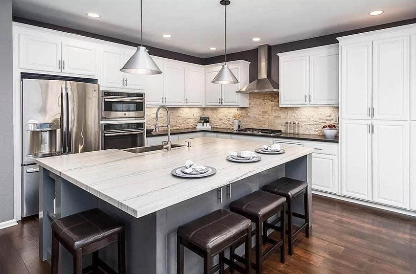 Kitchen with quartzite island white cabinets gray island