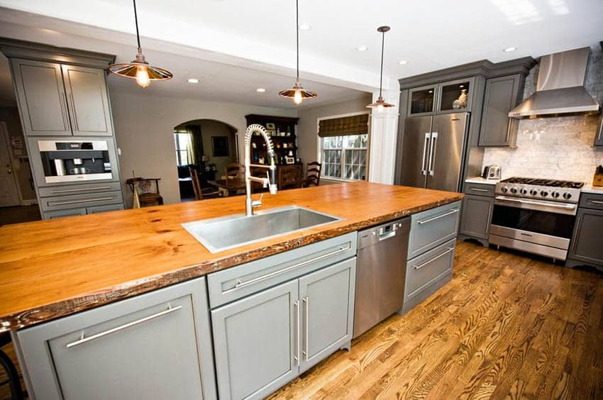 Kitchen with reclaimed countertop island with gray cabinets