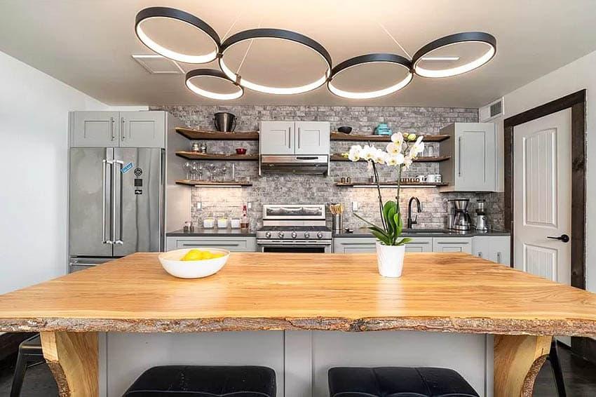 Kitchen with reclaimed wood counter island light gray cabinets brick wall backsplash