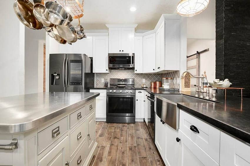 Kitchen with stainless steel counter island soapstone peninsula white cabinets
