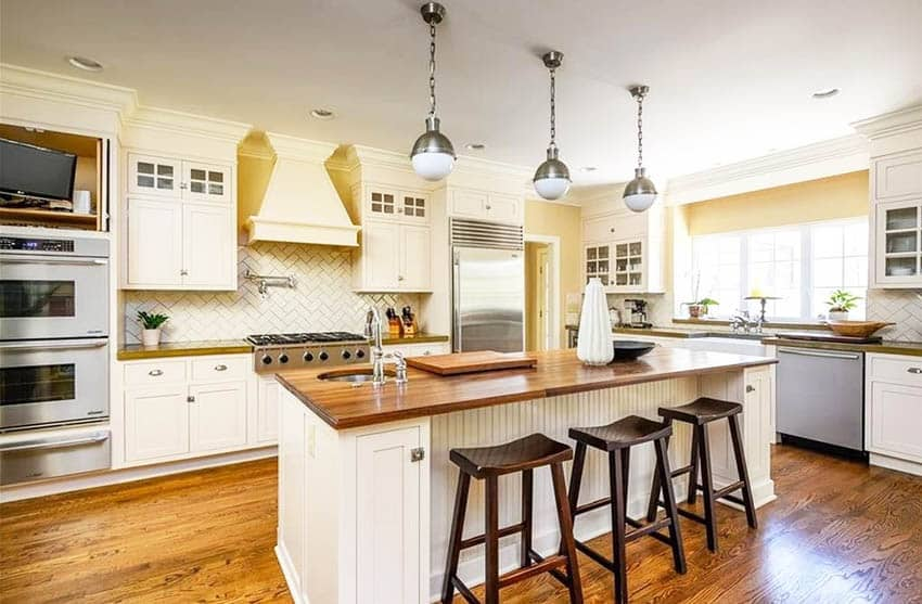 Kitchen with walnut countertop island and cream cabinets