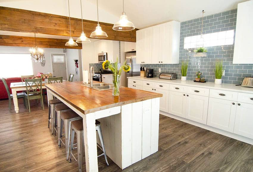 Kitchen with white cabinets and reclaimed wood countertop island