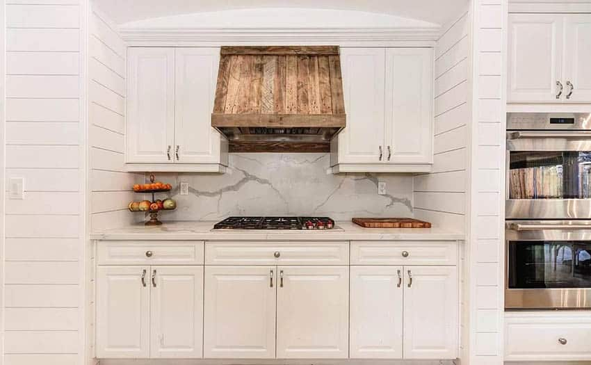 Kitchen with white cabinets reclaimed wood oven hood shiplap walls