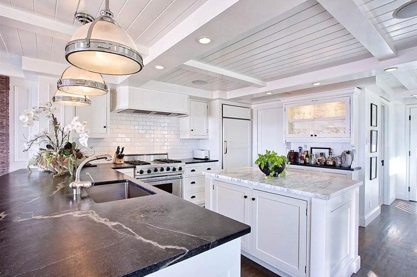 Kitchen with black soapstone peninsula and marble island with white cabinets and shiplap ceiling