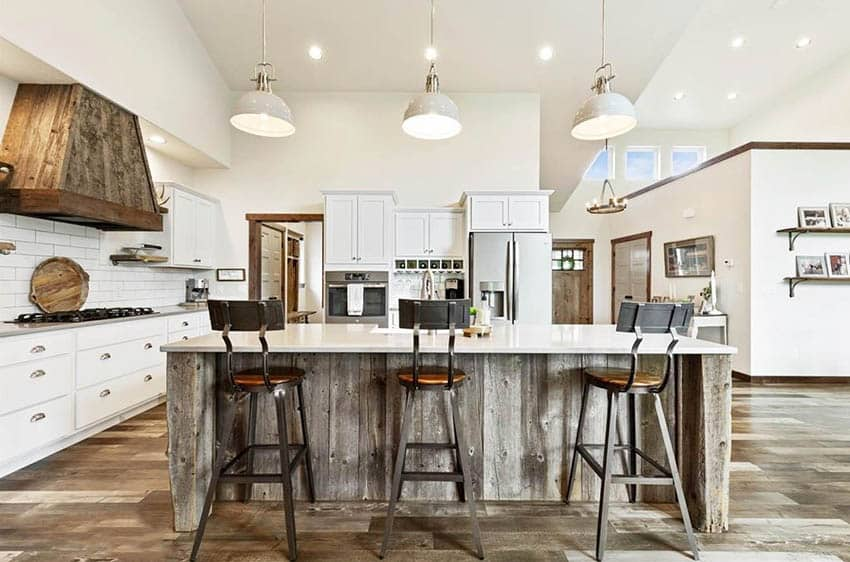 Luxury kitchen with reclaimed wood island wood oven hood and flooring white cabinets