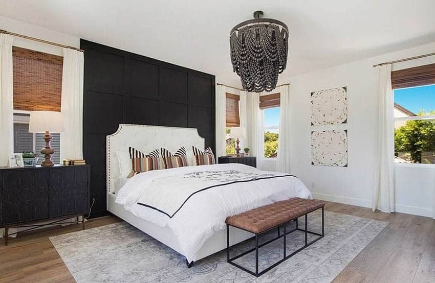 Modern farmhouse bedroom with black paneled accent wall behind bed beaded hanging chandelier