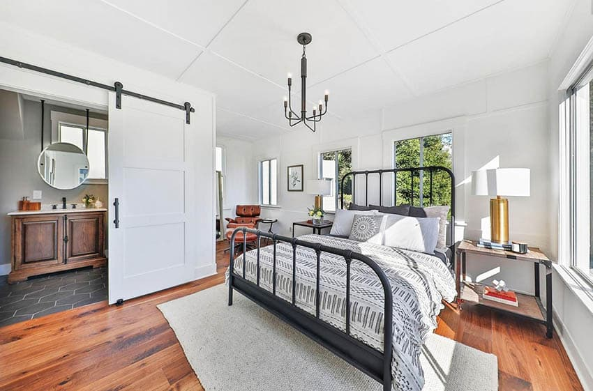 Modern farmhouse bedroom with dark metal finishes white sliding barn door to bathroom