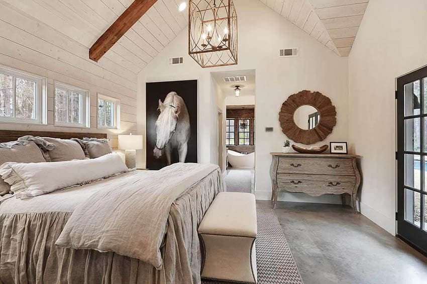 Modern farmhouse bedroom with gabled ceiling with beams shiplap walls concrete flooring