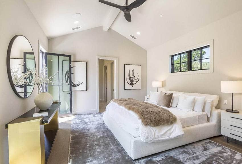 Modern farmhouse master bedroom with high ceiling large area rug black window door frames off white paint