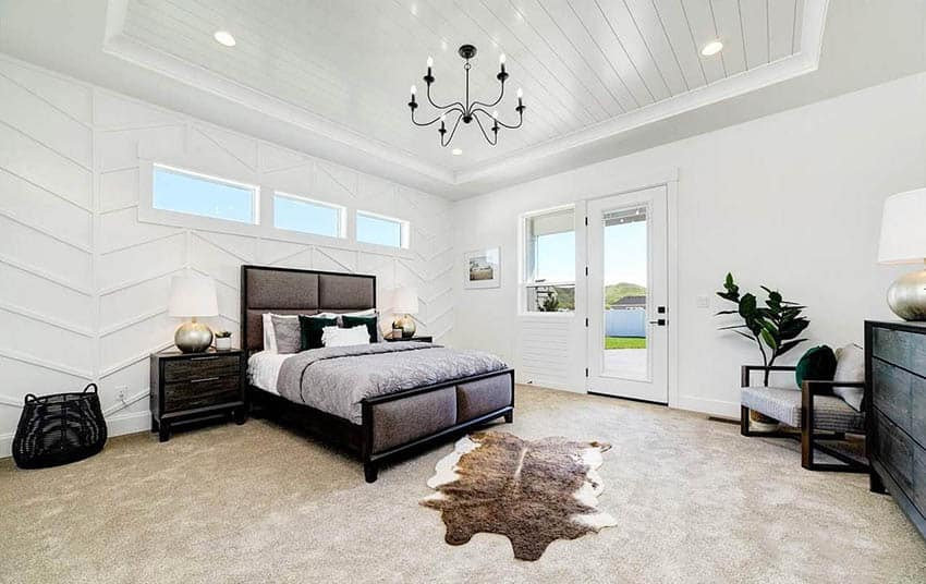 Modern farmhouse master bedroom with shiplap ceiling paneled walls and chandelier