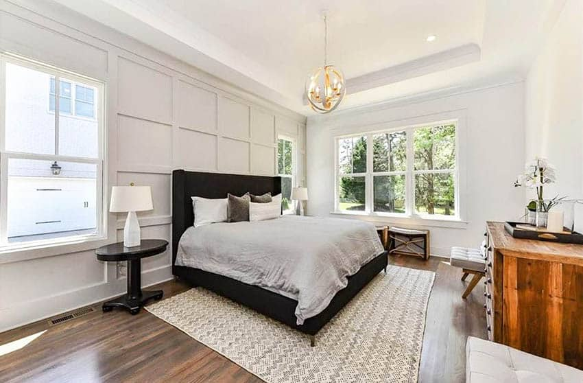 Modern farmhouse master bedroom with tray ceiling globe chandelier and paneled wall