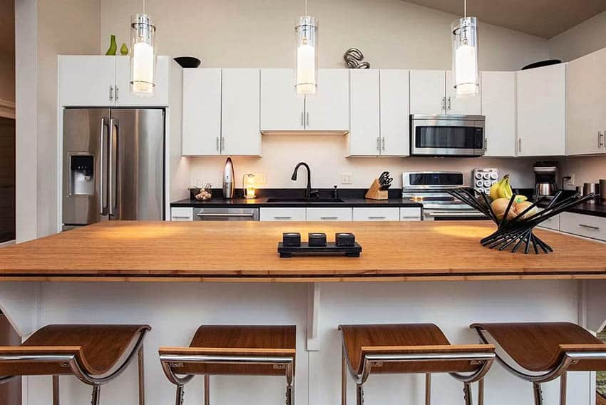 Modern kitchen with bamboo countertops white cabinets pendant lights