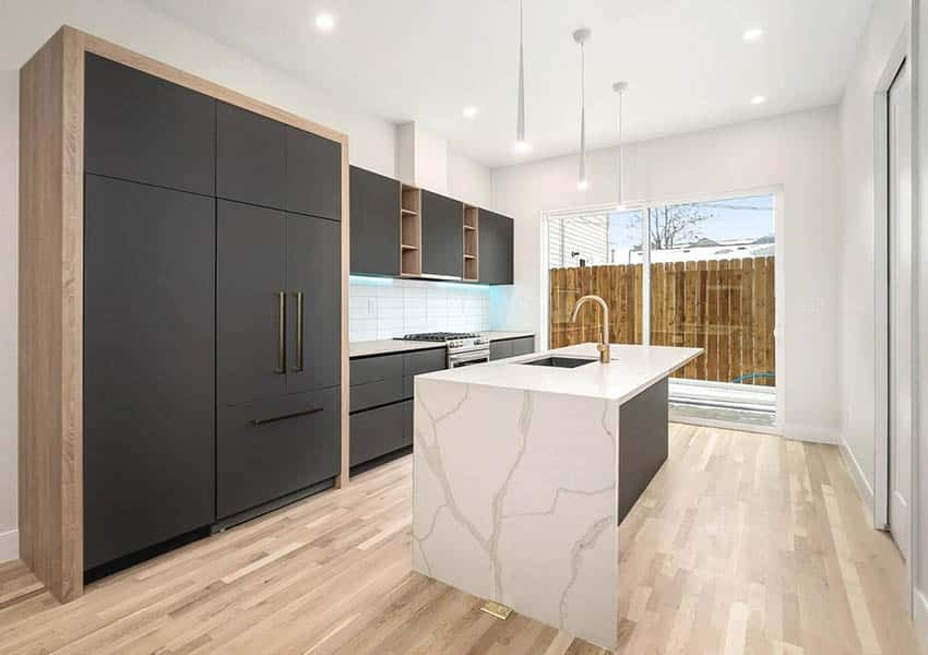 Modern kitchen with dark cabinets wood trim and quartz waterfall island