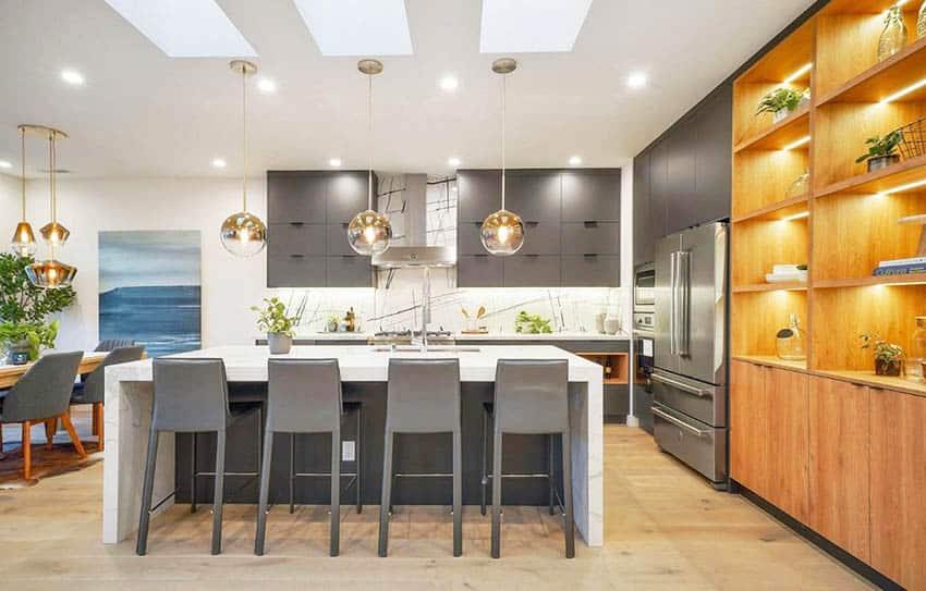 Modern kitchen with dark gray cabinets gray island with white quartz waterfall countertop