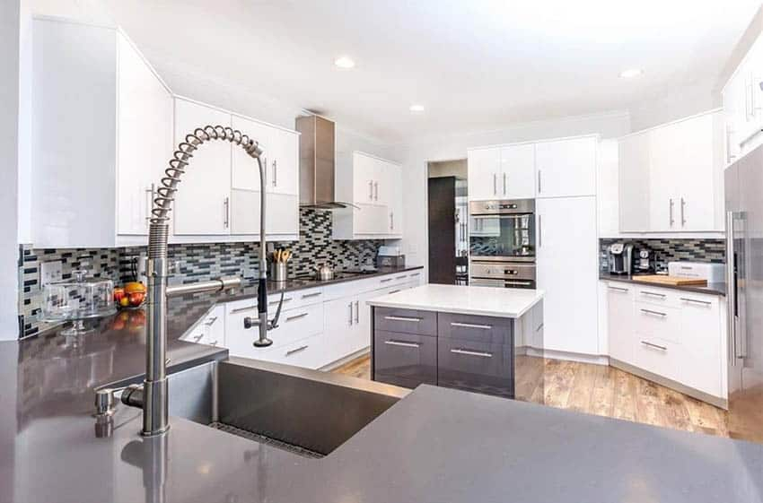 Modern kitchen with gray quartz peninsula and white quartz island white cabinets