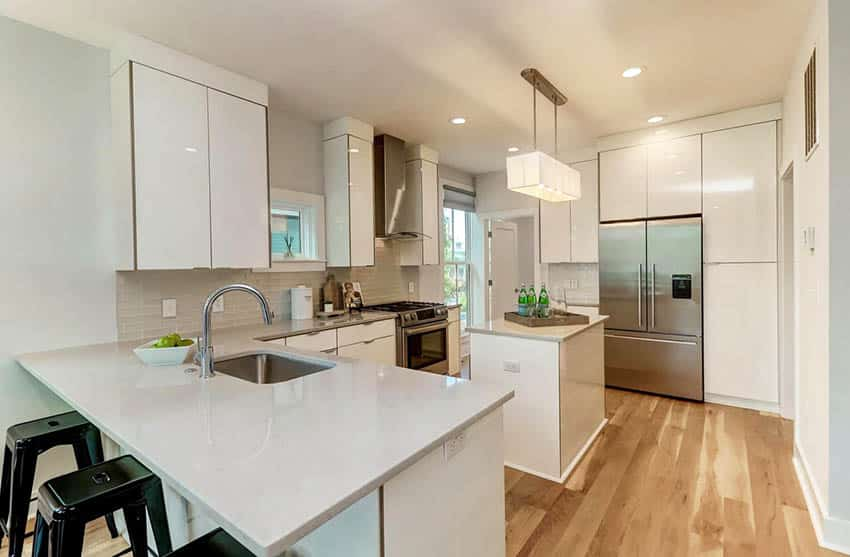 Modern kitchen with small dining peninsula island and quartz countertops white cabinets