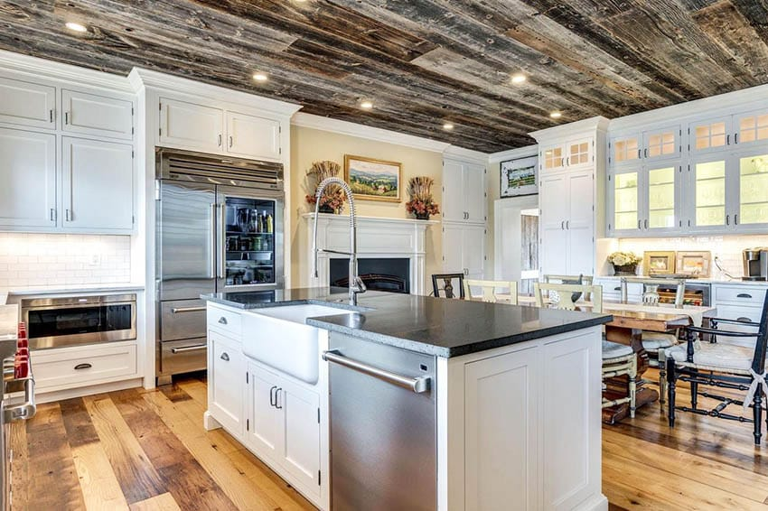 Open concept kitchen with American chestnut reclaimed wood flooring wood ceiling white cabinets