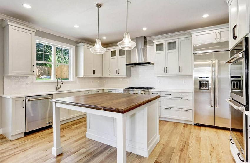 Open concept kitchen with custom walnut countertop island white cabinets