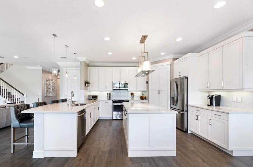 Open concept kitchen with large island and peninsula white quartz counters white cabinets