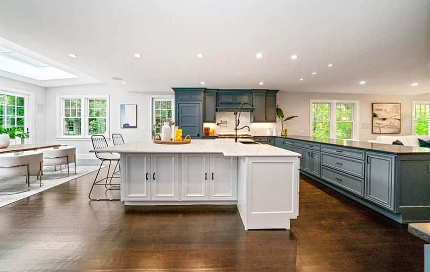 Open concept kitchen with white t shaped island large green cabinet peninsula wood flooring