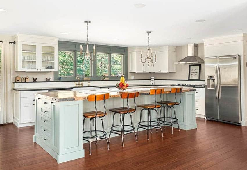Traditional kitchen with reclaimed wood counter light green island and white cabinets chandeliers
