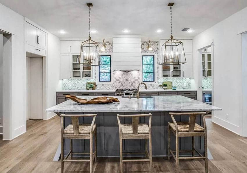 Transitional kitchen with dark gray base cabinets island and white upper cabinets marble counters and chandeliers