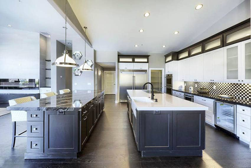 Transitional kitchen with large island and peninsula with black white cabinets agatha black granite and arctic white quartz