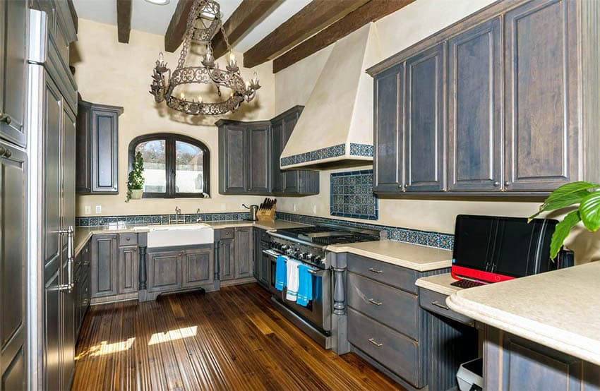 Tuscan kitchen with dark gray distressed cabinets rustic chandelier wood beams and bamboo flooring