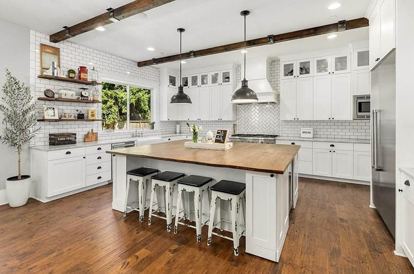 U shaped kitchen with reclaimed wood countertop island, white shaker cabinets, wood beams and flooring