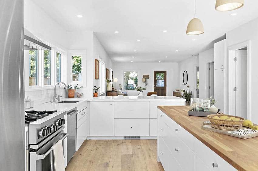White cabinet kitchen with butcher block island and quartz peninsula