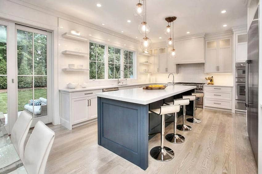 Beautiful kitchen with white quartzite countertops shaker style cabinets light wood flooring