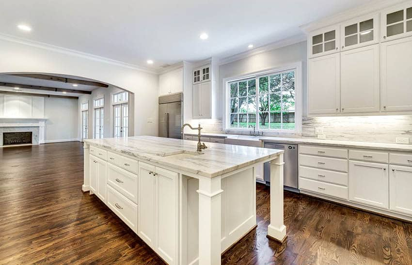Cape cod kitchen with white cabinets casement windows stone backsplash and crown molding