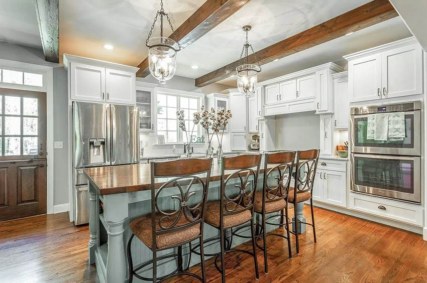 Cape cod kitchen with white cabinets light green island wood beam ceiling wood flooring