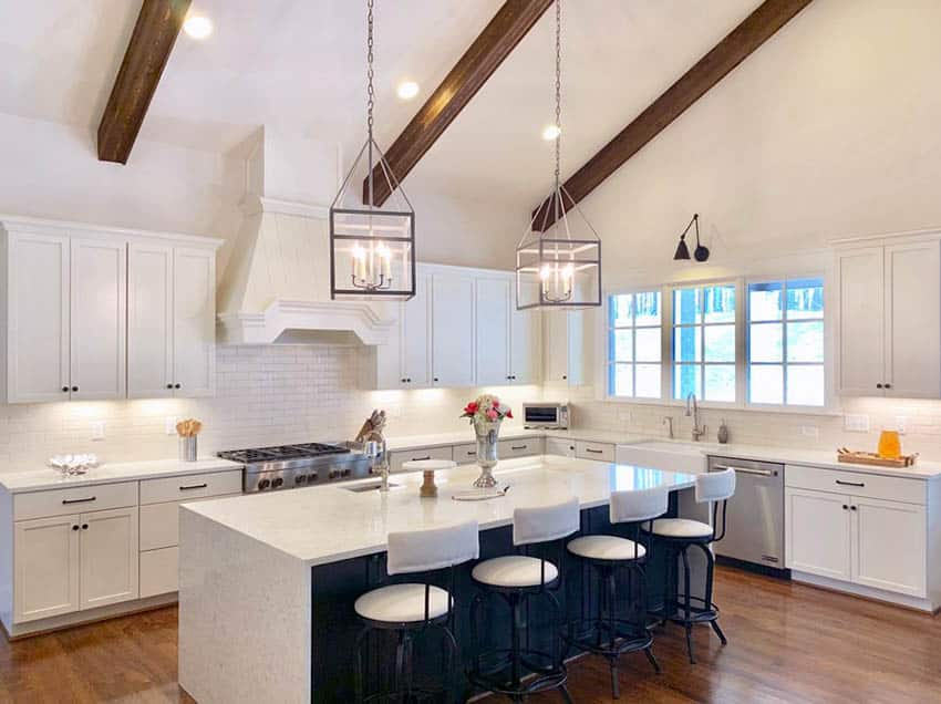 Cape cod style kitchen with vaulted ceiling wood beams white cabinets navy island white quartz counters